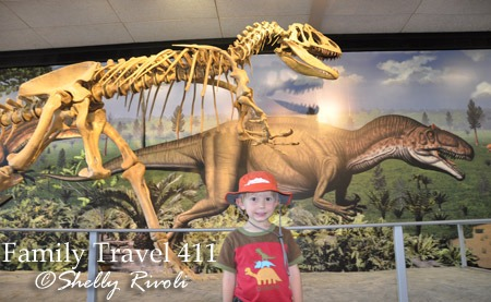"""A mural behind this skeleton shows what paleontologists believed it looked like """"in the flesh,"""" as a park ranger standing nearby explains why."""