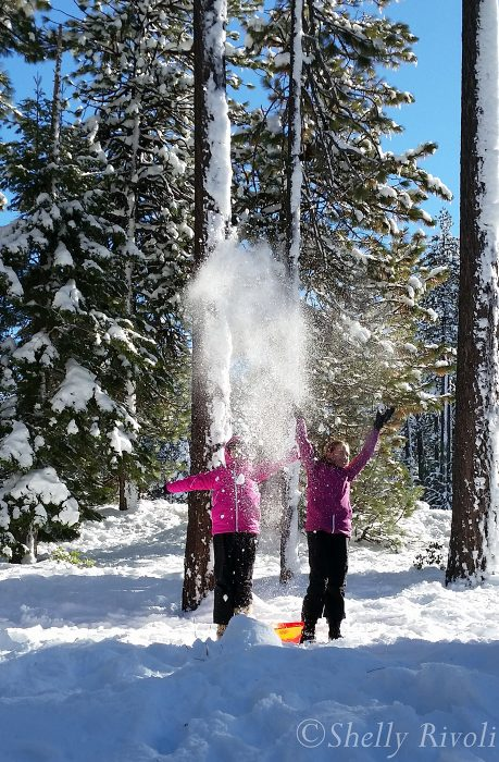 two girls, sisters, throw snow into the air in the woods near Lake Tahoe