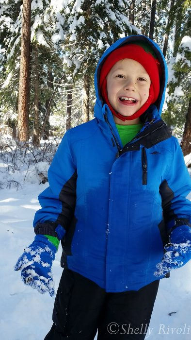 boy smiles in snow in woods eating snow near Tahoe