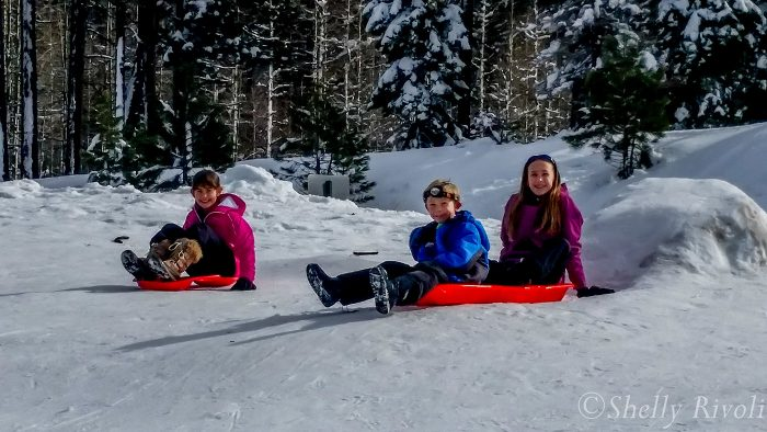 Three kids sledding at Tahoe