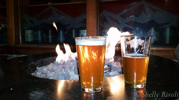 Two pints of beer by a blazing fire at Base Camp Pizza at night in South Lake Tahoe