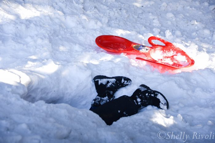 only boots stick out from hole in snow dug by kid