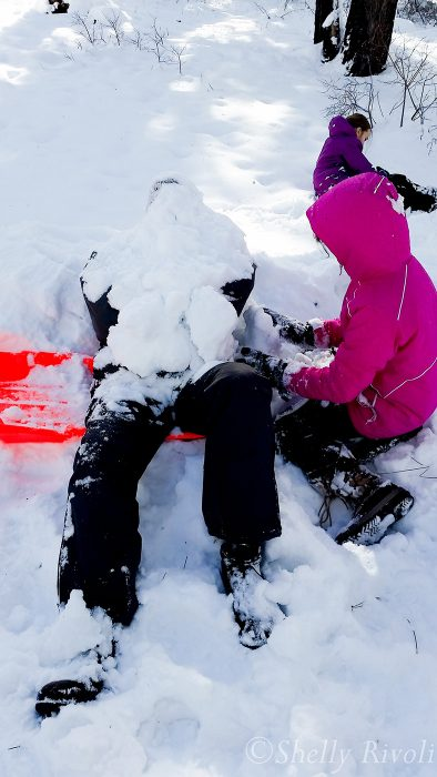 Dad getting packed with snow by kids
