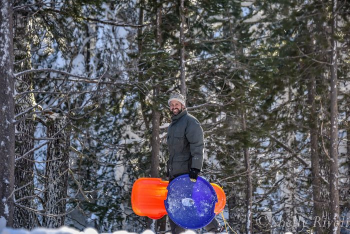Smiling dad carrying snow sleds near South Lake Tahoe