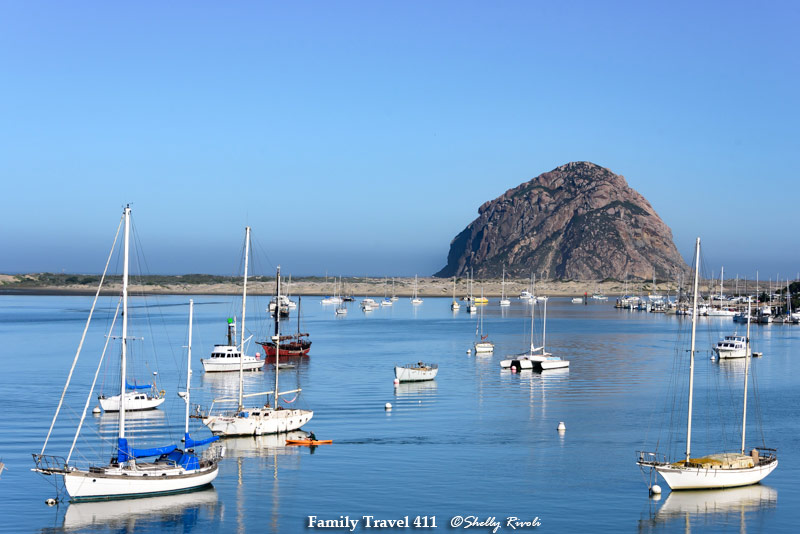 Morro Bay on a calm morning with sailboats anchored and Morro Rock in the background