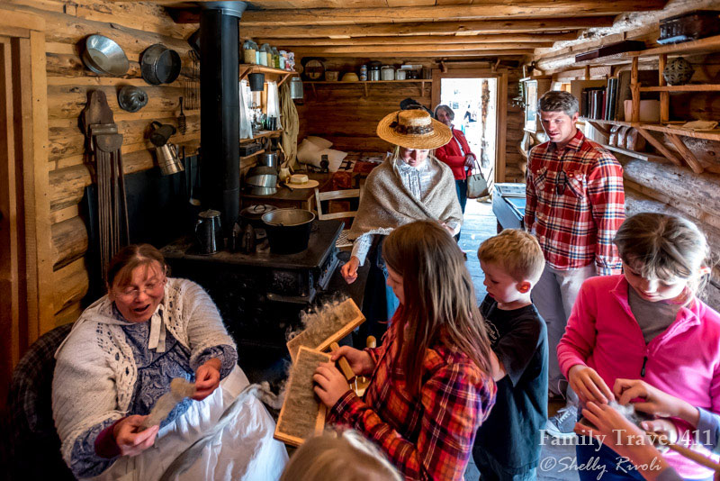 Costumed interpreters teach 21st century visitors to card wool at the Miller Ranch.