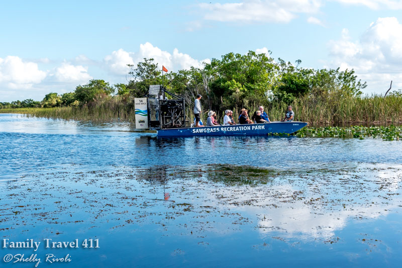 A small airboat drifts past trees as passengers look for birds returning after Hurricane Irma.